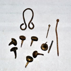 7 small brass fasteners, 1 brass eye for clothes hook, 2 brass straight pins, 2 narrow flakes from brass wash